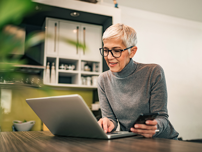Older woman sitting at table working on laptop