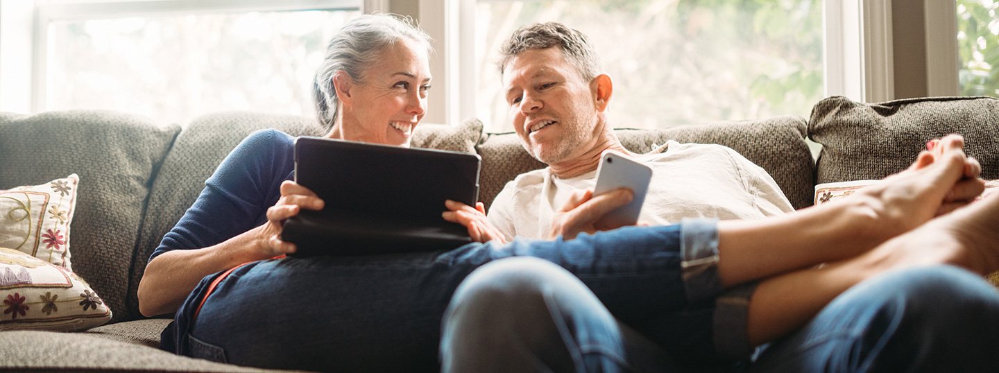 Middle aged man and woman on sofa looking at a tablet