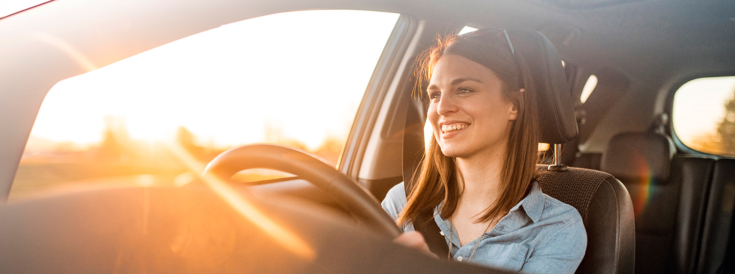 Woman driving her car in the sunset