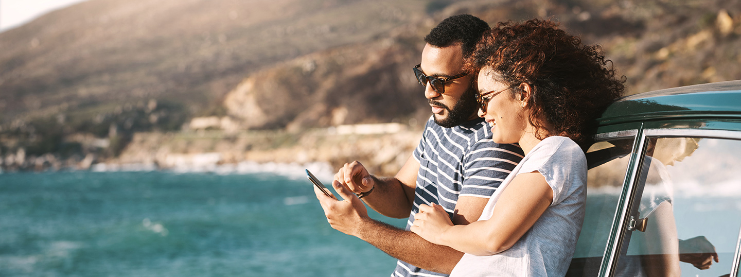 Couple leaning agains their car by the coast, looking at a smartphone