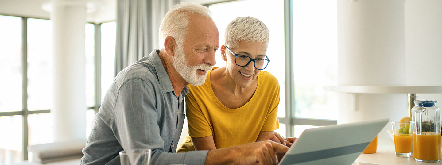 Older couple sitting in their kitchen looking at their computer