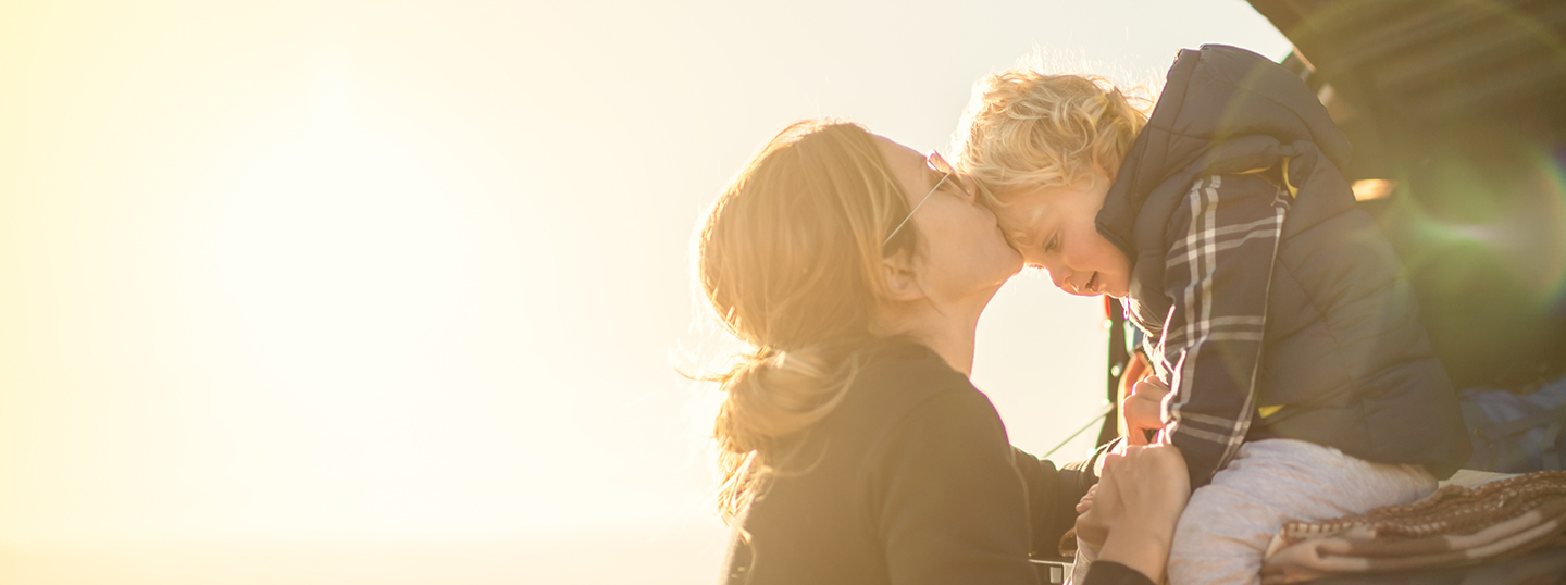 Woman kissing child on forehead in the sunshine