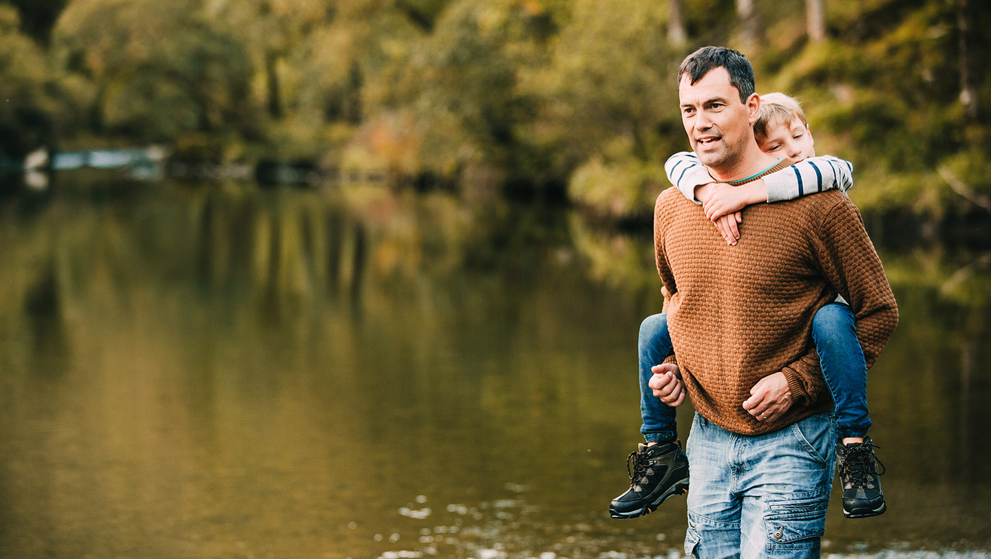 Middle aged man carrying his son in front of a lake in the woods