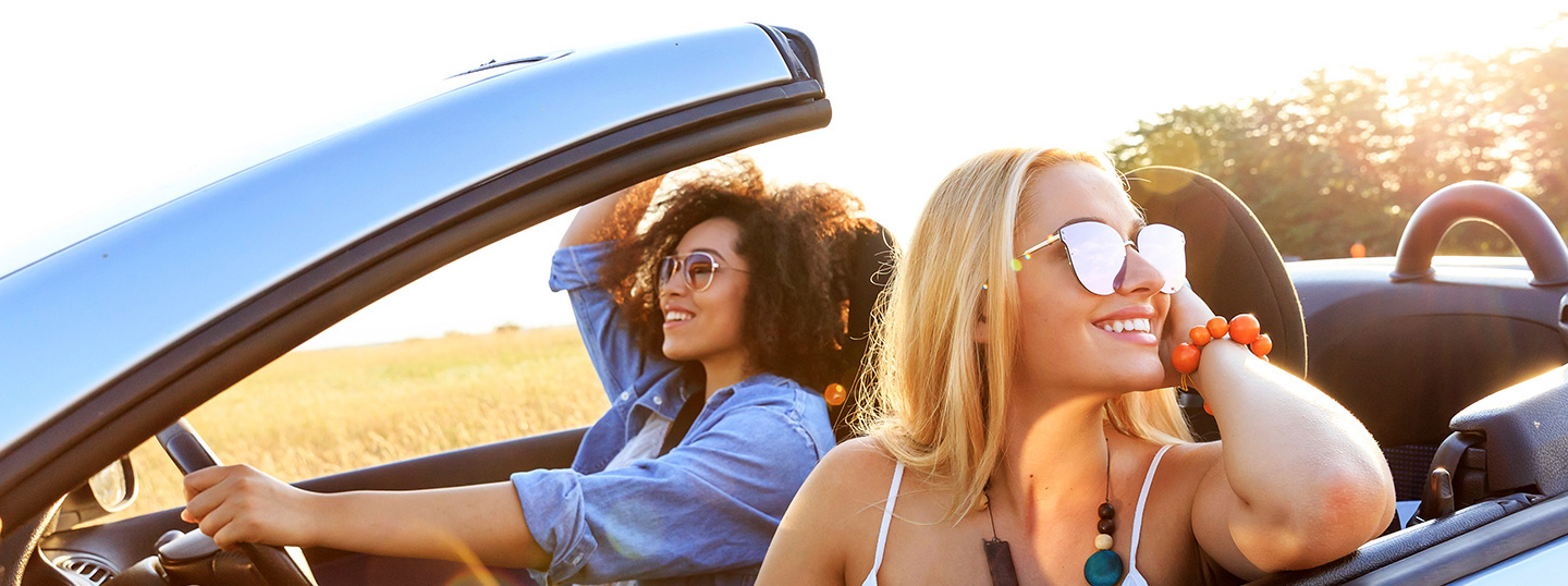 Two women smiling whilst driving in a convertible in the sun