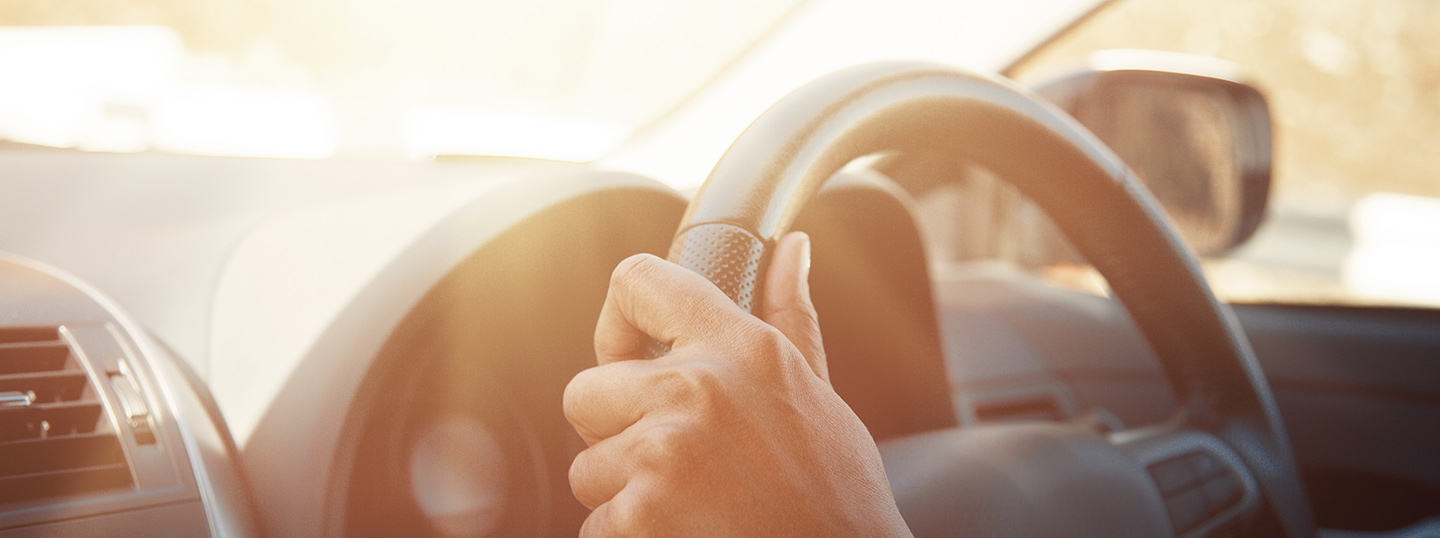 Close up of hands on a steering wheel in the sun