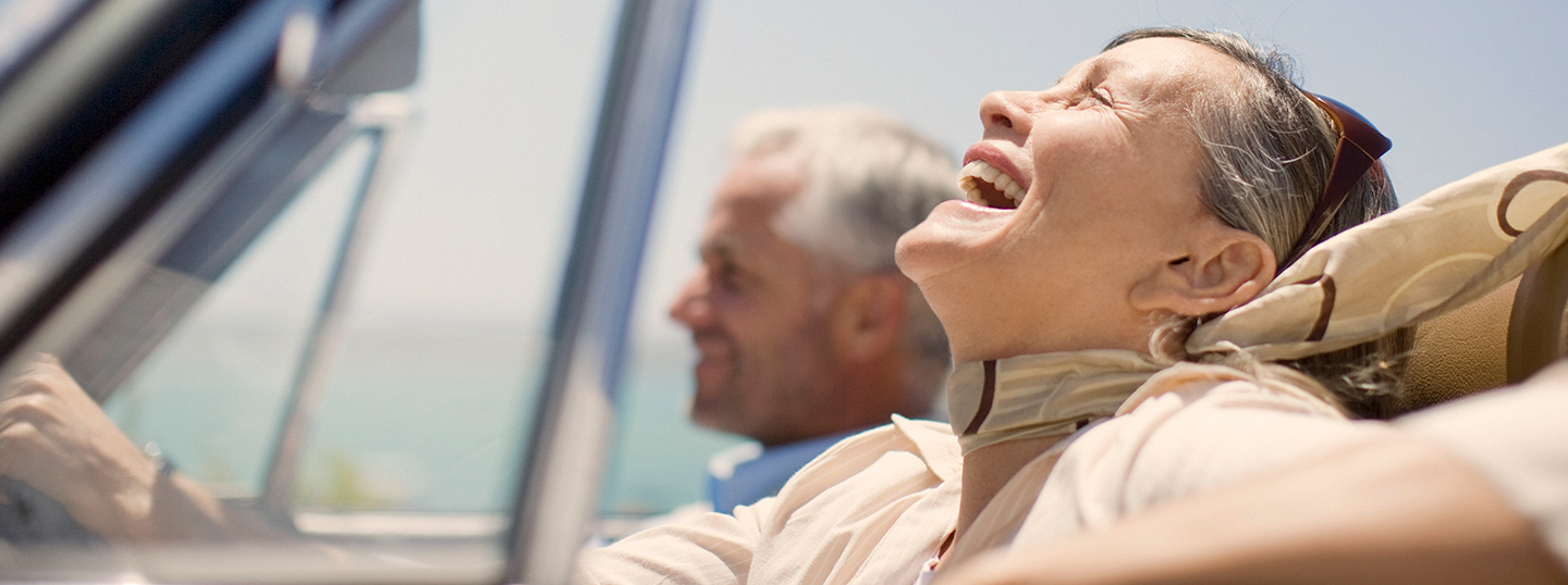 Older couple laughing whilst driving in a convertible in the sun