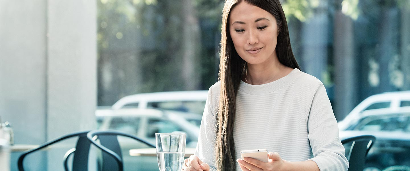 Woman sitting in cafe looking at phone