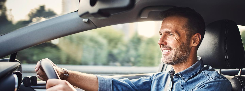 Man smiling while driving his car