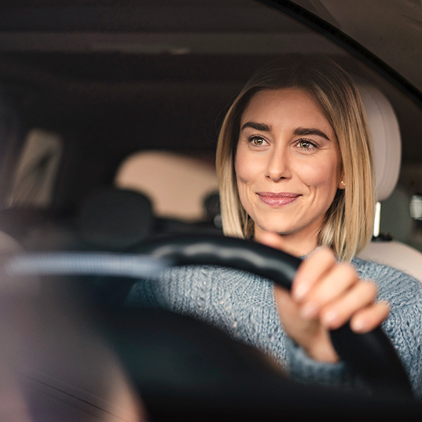 Close up of woman smiling while driving her car