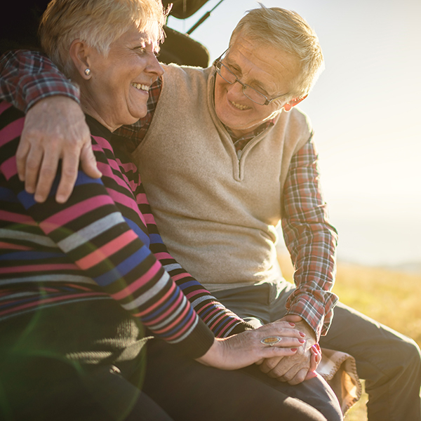 Older couple hugging in their boot in the sunshine and smiling at each other