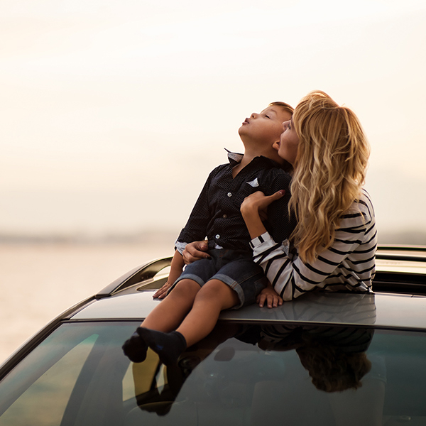 Woman hugging her son, who's sitting on the car's roof, through the sunroof