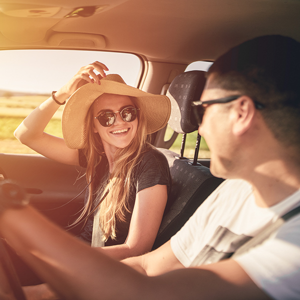 Young couple laughing at each other whilst driving in the sun