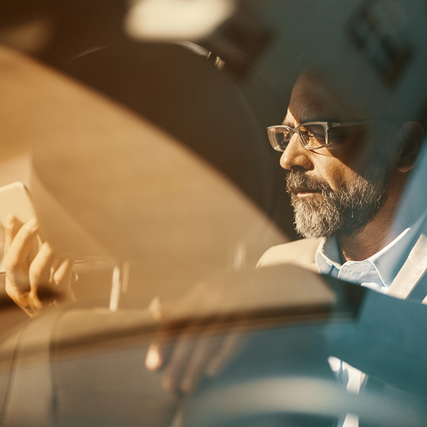 Man photographed through the reflections of a windscreen of a car