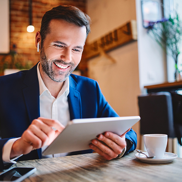 Man in suit working in a cafe with his ipad